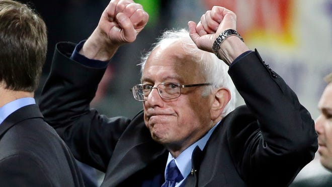 Democratic presidential candidate Sen. Bernie Sanders, I-Vt., pumps his fists as he leaves the field after speaking at a rally Friday, March 25, 2016, in Seattle.
