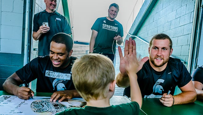 MSU tightend Matt Sokol, right, high fives a young fan during Meet the Spartans Tuesday August 16, 2016 at Spartan Stadium in East Lansing.