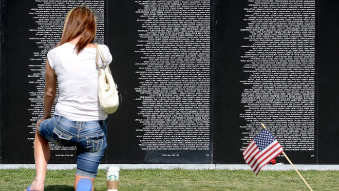 Stephanie Milner is moved to tears as she kneels before the thousands of names etched into a traveling Vietnam Veterans Memorial Wall at Spring Canyon Community Park in Fort Collins in 2013.