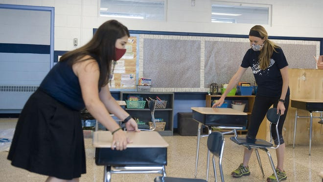Immaculata Catholic School Principal Margaret Beale, left, helps fourth-grade teacher Ella Morgan, right, space her classroom's desks to six feet apart on Aug. 18 in preparation for the new school year on Sept. 8, when the school will start the year person-to-person.