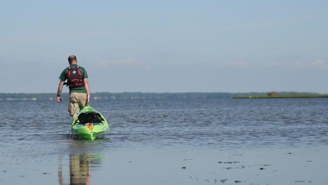 Alex Peterson, Delaware Seashore State Park guide, walks his kayak after hitting low tide.