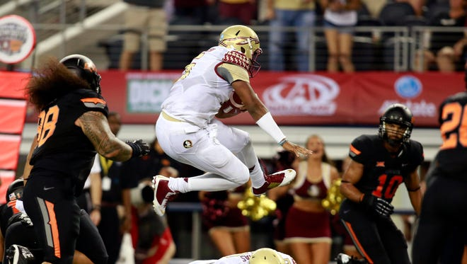 Quarterback Jameis Winston leaps over a teammate on his way to a second-half touchdown.