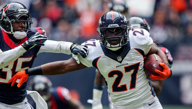 Dec 22, 2013; Houston, TX, USA; Denver Broncos running back Knowshon Moreno (27) runs during the first quarter as Houston Texans safety Eddie Pleasant (35) attempts to make a tackle at Reliant Stadium. Mandatory Credit: Troy Taormina-USA TODAY Sports ORG XMIT: USATSI-133020 ORIG FILE ID:  20131222_pjc_at5_094.JPG