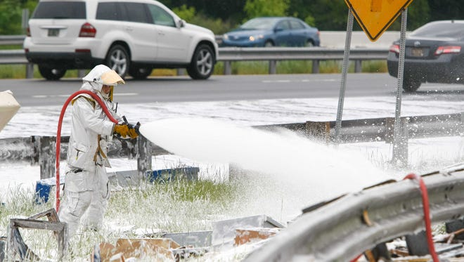 Dominic Pizzo with Station 33 Delaware Air Guard uses foam to spray on the millions of bees along I-95 near Newark, Delaware Wednesday, May 21, 2014.