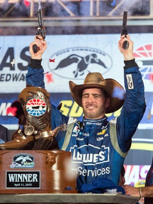 Jimmie Johnson fires the ceremonial six shooters after winning the Duck Commander 500 Saturday night at Texas Motor Speedway.