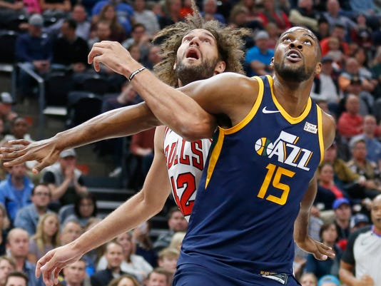 Utah Jazz forward Derrick Favors (15) and Chicago Bulls center Robin Lopez works for position under the basket during the first half of an NBA basketball game Wednesday, Nov. 22, 2017, in Salt Lake City. (AP Photo/Rick Bowmer)
