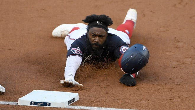 Washington Nationals' Josh Harrison slides into third base on a single by Eric Thames during the second inning of a baseball game against the Tampa Bay Rays, Monday, Sept. 7, 2020, in Washington. (AP Photo/Nick Wass)