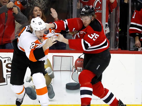 Philadelphia Flyers right wing Dale Weise, left, and New Jersey Devils defenseman Seth Helgeson fight during Thursday's game.