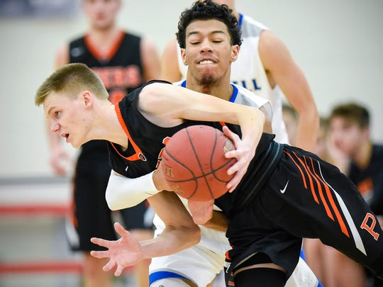 Sartell's Preston Simpson tries to seal the ball from Princeton's Tate Laabs in overtime Friday, Dec. 29, during the Breakdown Granite City Classic boys basketball tournament at Apollo High School.