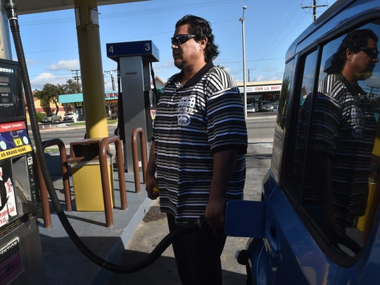 Alfred Hurtado, of Oxnard, fills his tank on Monday before the Thanksgiving holiday. According to AAA, 49 million people are expected to travel 50 miles or more this week. Most will drive.