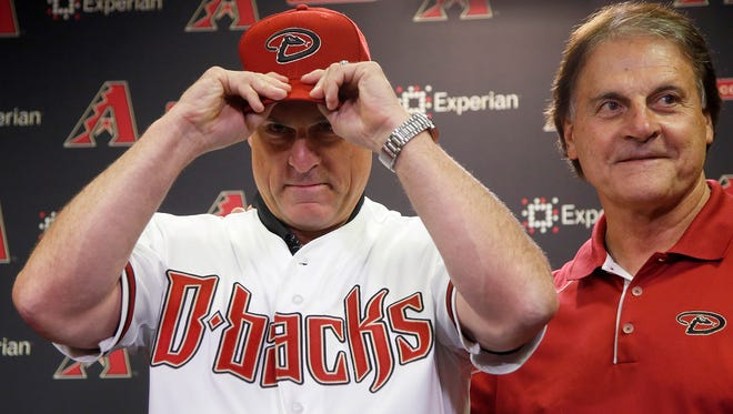 New Arizona Diamondbacks manager Chip Hale (left) puts on a Diamondbacks hat as he is introduced by Chief Baseball Officer Tony LaRussa during a news conference on Monday, Oct. 13, 2014, in Phoenix.