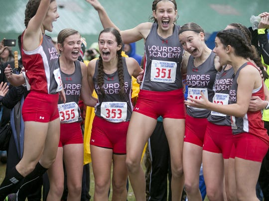 Lourdes Academy celebrates their first place in the Division 3 girls race at the WIAA State Cross Country Meet at the Ridges Country Club in Wisconsin Rapids on October 31. It was the third straight year the Knights have won the state title.