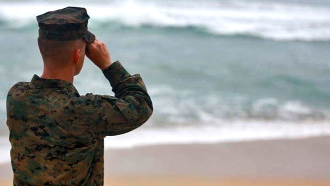 This Friday, Jan. 15, 2016 photo provided by the U.S. Marine Corps shows a Marine Officer attached to Marine Heavy Helicopter Squadron 463 uses binoculars to search for debris of a helicopter mishap in Haliewa Beach Park, Hawaii. Rescuers battled winds of up to 23 mph and waves up to 30 feet as they searched for 12 Marines who are missing after two helicopters they were in crashed off the Hawaiian island of Oahu.(Cpl. Ricky S. Gomez/U.S. Marine Corps via AP)