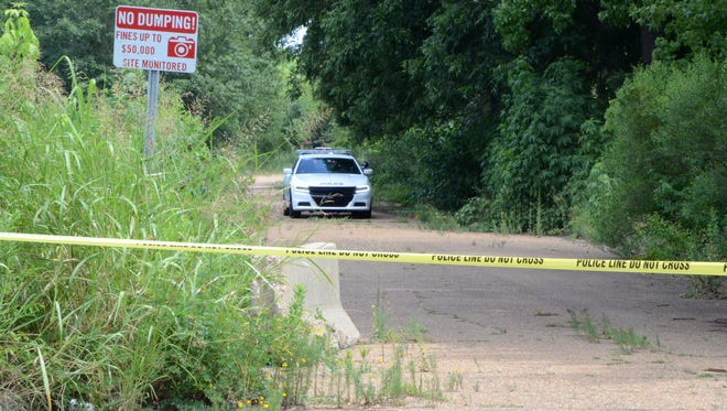 A Jackson police car drives up abandoned Bay Street where a burned body was found Thursday.