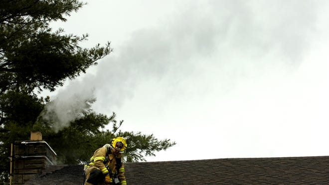 A firefighter climbs down from the roof after inspecting the chimney and surrounding attic area Tuesday. Staunton and Augusta County firefighters responded to a chimney fire at 826 New Hope Road in Staunton Tuesday, January 6 2009. Lt. Perry Weller of the Staunton Fire Dept. pointed to creosote build up in the chimney as the cause for the fire. Though the fire did not spread to the attic, the chimney will have to be replaced, said Weller.