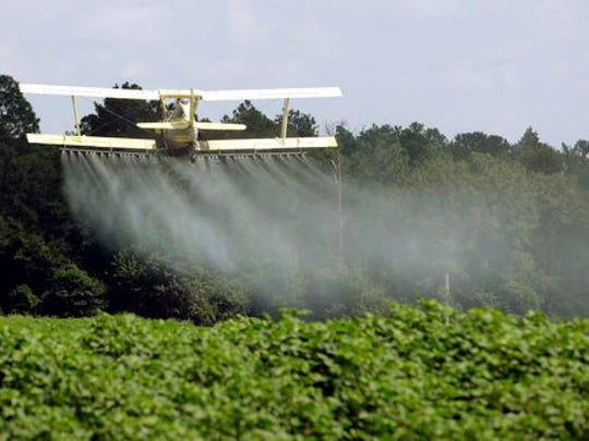 A crop duster sprays a field of crops.