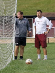 Elmira girls soccer coach Zach Sarno, left, talks with Express boys soccer coach Derek Hamilton during the opening day of practices Aug. 14 at Ernie Davis Academy.