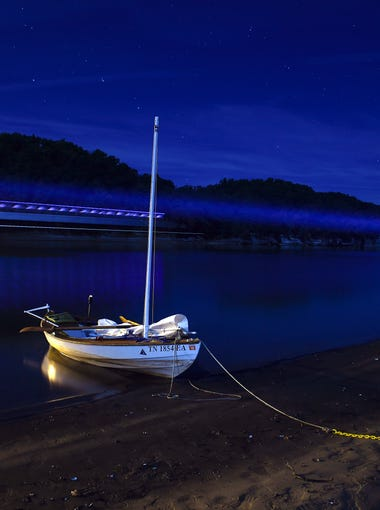 John Guider's boat the Adventure II rests on the bank of the Tennessee River Tuesday, Oct. 11, 2016, in Parsons, Tenn. The light from a tugboat and barge streaks through the photograph as it makes it way down the Tennessee River.