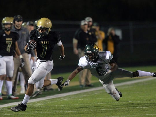 West High's Andre White breaks a tackle as he runs