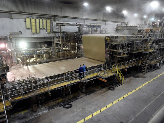 International Paper mill team members Scott Abner and Ronnie Todd inspect paper being made on the wet end at the plant in Henderson recently.  The plant makes almost 700 tons of paper a day by using recycled boxes and making them into paper.