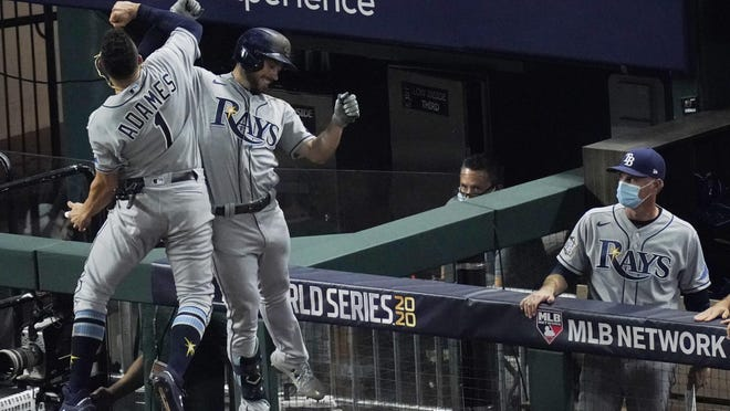 Tampa Bay Rays' Brandon Lowe celebrates a two-run home run with Willy Adames during the fifth inning in Game 2 of the baseball World Series against the Los Angeles Dodgers Wednesday, Oct. 21, 2020, in Arlington, Texas.