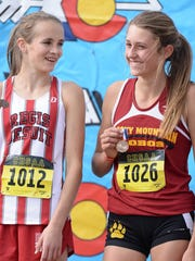 Julia Schlepp, right, of Rocky Mountain High School, celebrates with Isalina Colsman of Regis on the awards stand after placing ninth in the girls 5A state cross country meet Saturday in Colorado Springs.