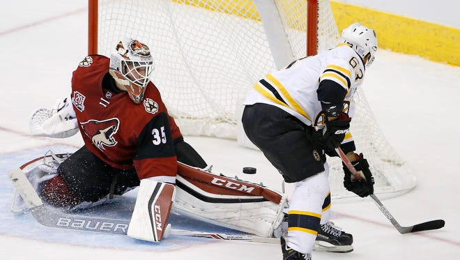 Boston Bruins left wing Brad Marchand (63) has his shot blocked by Arizona Coyotes goalie Louis Domingue (35) during the second period of an NHL hockey game Saturday, Nov. 12, 2016, in Glendale, Ariz. The Bruins defeated the Coyotes 2-1.
