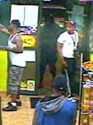 Detroit police are seeking the identity of a male seen at right in a white T-shirt in connection with a homicide.