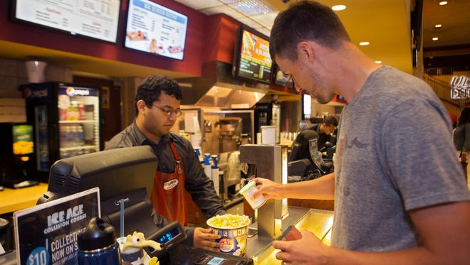Keenan Quick (right) salts some popcorn held by cashier Louise Cruz (left). Loyalty members also get free refills on soft drinks, $5 in rewards for every $100 spent and online ticket fees waived, a $1.50 value per ticket.