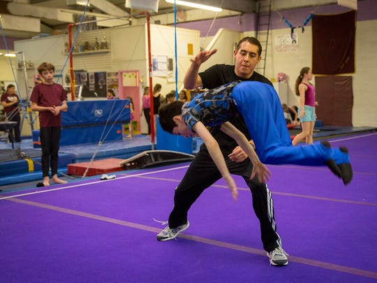 Retired gymnast Chris Lambert helps out 11-year-old Aaron Crawford with a spin at the Cruces Gymnastics Academy as fellow student, 12-year-old Charles Dillaway, left, looks on.