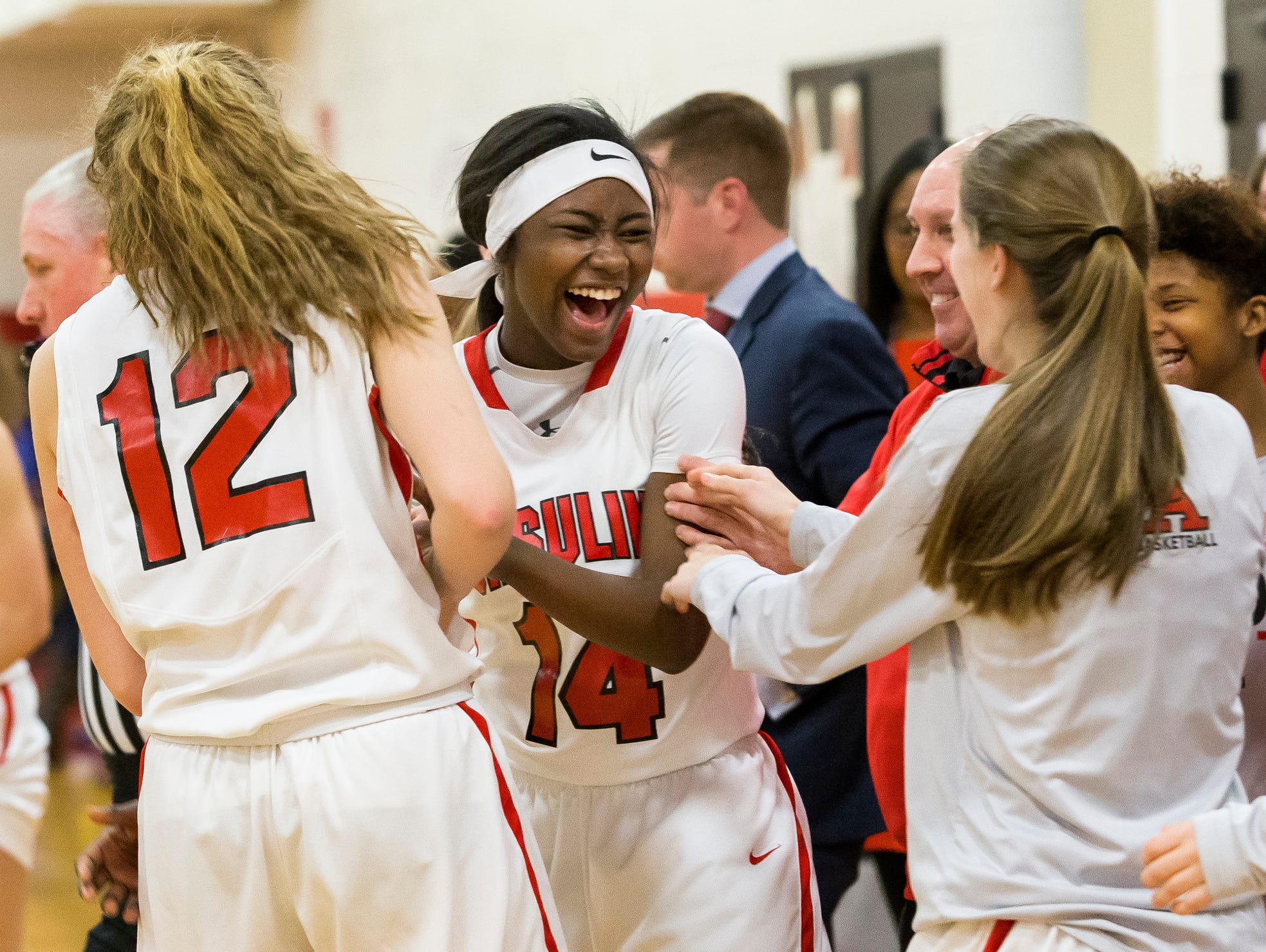 Ursuline's Kryshell Gordy (No. 14) laughs with her teammates after a missing a shot in the second half of Ursuline's 50-40 win over Sanford at Ursuline Academy on Thursday night.