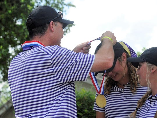Wylie girls golf coach Mike Campbell puts a bronze medal around Maddi Olson after the Lady Bulldogs finished third at the 2018 UIL Class 4A state tournament at the Slick Rock Golf Course at Horseshoe Bay in Marble Falls. Olson finished third individually along with the third-place team finish as a sophomore.