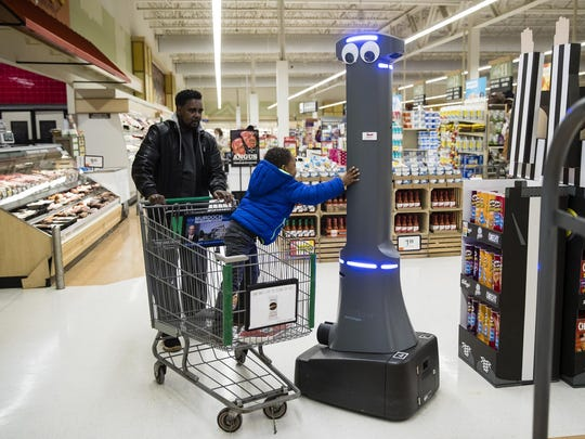 William Rucker and his grandson Justice, 4, say hello to a robot named Marty as it cleans the floors at a Giant grocery store in Harrisburg, Pa., Jan. 15, 2019.