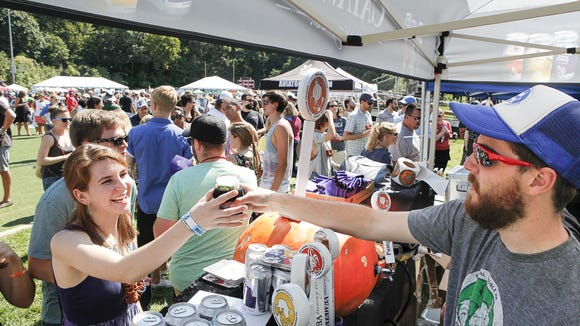 Sydney Lierz, left is handed a glass of  beer at the  Brewgrass Festival Saturday at Memorial Stadium. The festival  benefited Big Brothers and Big Sisters of Western North Carolina.
