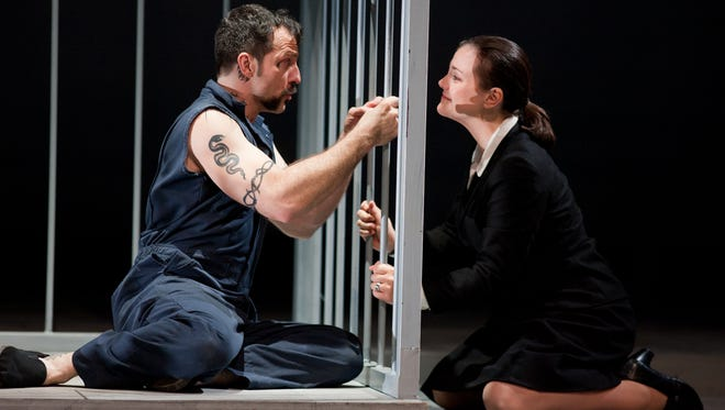 Joseph De Rocher, played by baritone David Adam Moore, is comforted by Sister Helen Prejean, played by mezo-soprano Elise Quagliata, after he accepts his guilt in a double murder in the Des Moines Metro Opera's production of Dead Man Walking.