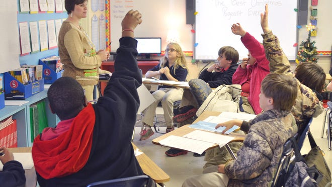 Riverside Elementary School third grade teacher Jennifer McKnight, left, receives questions from students during a writing assignments Tuesday in Avon.