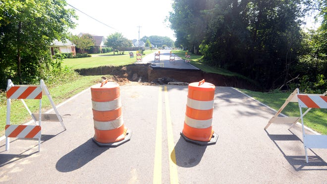 Flash flooding caused a part of East University Parkway between Woodard Drive and McIntosh Drive in North Jackson to cave in.