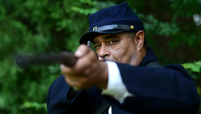 Michael Cherry stands in a Civil War era replica uniform with gun at his home in Jackson on Wednesday. Cherry hopes to teach African-American history during the Civil War with an exhibit he'll be featuring at the African Street Festival this weekend at the Jackson Fairgrounds.
