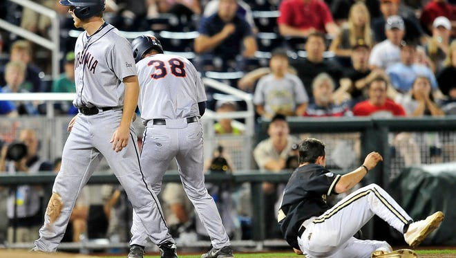 Vanderbilt's Tyler Campbell, right, collides with Virginia's Mike Papi (38) in the 9th inning at the College World Series at TD Ameritrade Park in Omaha, Neb., Tuesday, June 24, 2014. Vanderbilt lost 7-2.