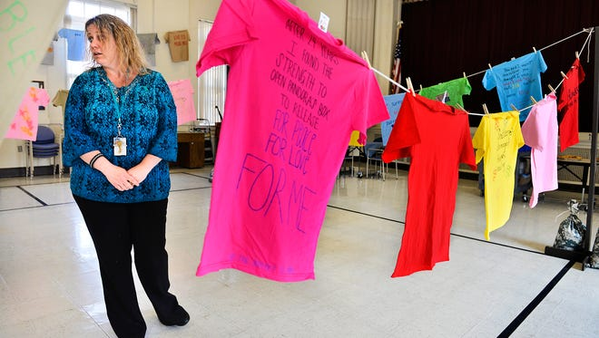 Joy Finkelson, military sexual trauma coordinator at the St. Cloud VA Health Care System, talks about the Clothesline Project Tuesday in the VA Auditorium. T-shirts, 31 of them in all, were decorated anonymously by those affected by sexual assault as a means of expression and hung on a clothesline as a visible reminder of the crime's lasting effects.