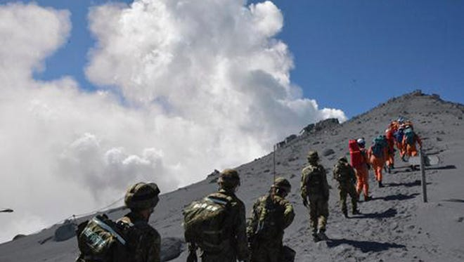 Japan Ground Self-Defense Force personnel head for the summit of Mount Ontake on Sunday.