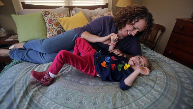 Kathryn Hintz plays with her daughter Morgan, 2, at their home in North Salem, N.Y., on Tuesday, Nov. 19, 2013. Morgan was born with Dravet syndrome as well as with  chromosome abnormalities that have left her with developmental delays.