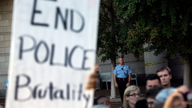A member of the Clayton, Mo., police department stands watch as protesters gather outside the Buzz Westfall Justice Center on Wednesday, Aug. 20, 2014, in Clayton, Mo.