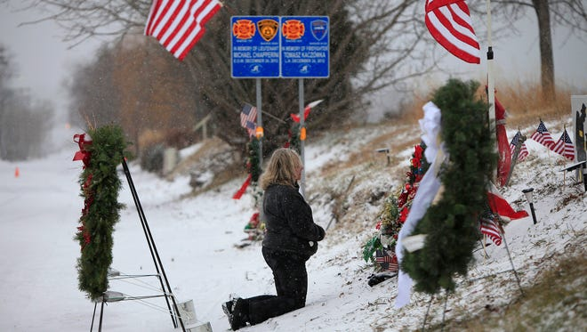 Regina Schreiber-Pinkney, of Webster, N.Y., kneels at the memorial site on Lake Road in Webster on Tuesday, Dec. 24, 2013. On Tuesday, people gathered at the spot where four firefighters were shot Dec. 24, 2012. Two firefighters were killed in the gun battle with William Spengler Jr.