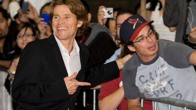 """Actor Willem Dafoe, left, laughs with a fan on the red carpet before the screening of """"Antichrist' during the Toronto International Film Festival in Toronto on Sept. 10, 2009."""