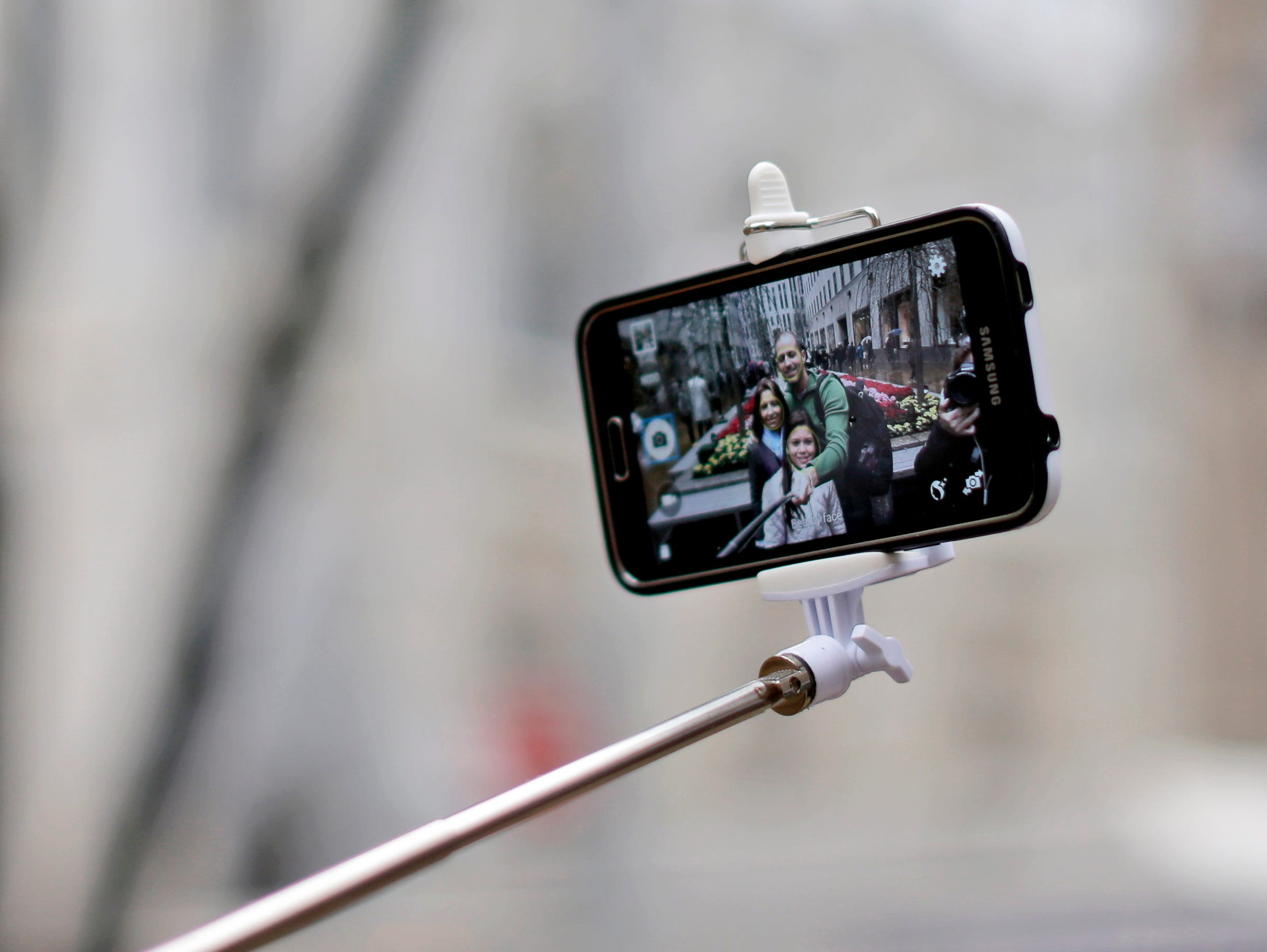Visitors use a selfie stick to take a photo of themselves in New York.