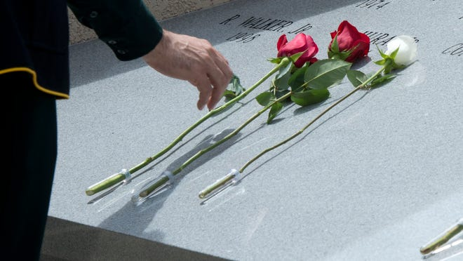 Flowers of remembrance are placed on a memorial to fallen officers outside the Escambia County Sheriff's Office during the department's annual law enforcement memorial ceremony Wednesday morning June 28, 2014.