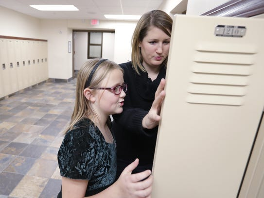 Rhiannon Ness, 12, shows Carly Resch her locker before