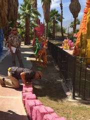 City of Palm Springs building inspector David Salas kneels down to get a closer look during an inspection of the Robolights display on Thursday, June 9, 2016.