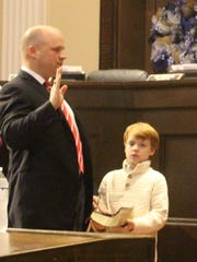 New Anderson County Councilman Craig Wooten takes the oath of office as his 8-year-old son, Joe Riley Wooten, holds the Bible.